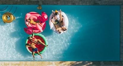 Aerial view of young people on summer vacation enjoying on fun inflatable floats in swimming pool. Group of friends relaxing on air mattresses in pool.