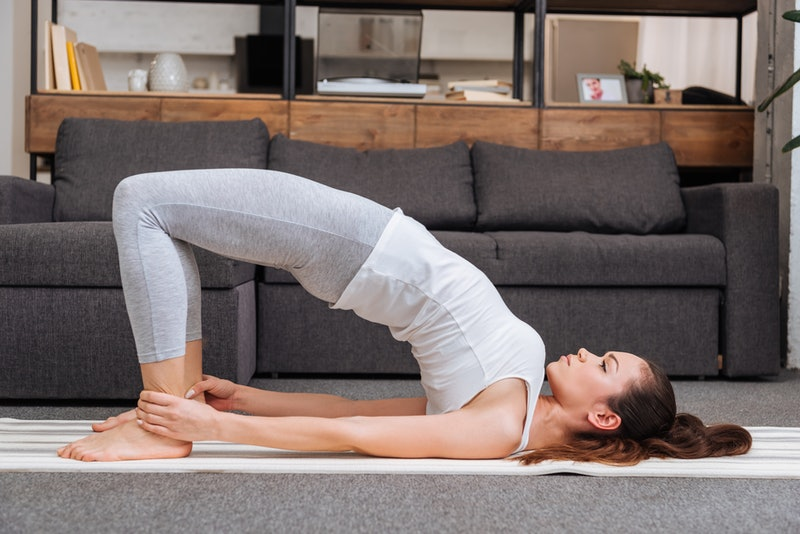 woman practicing bridge pose at home in living room