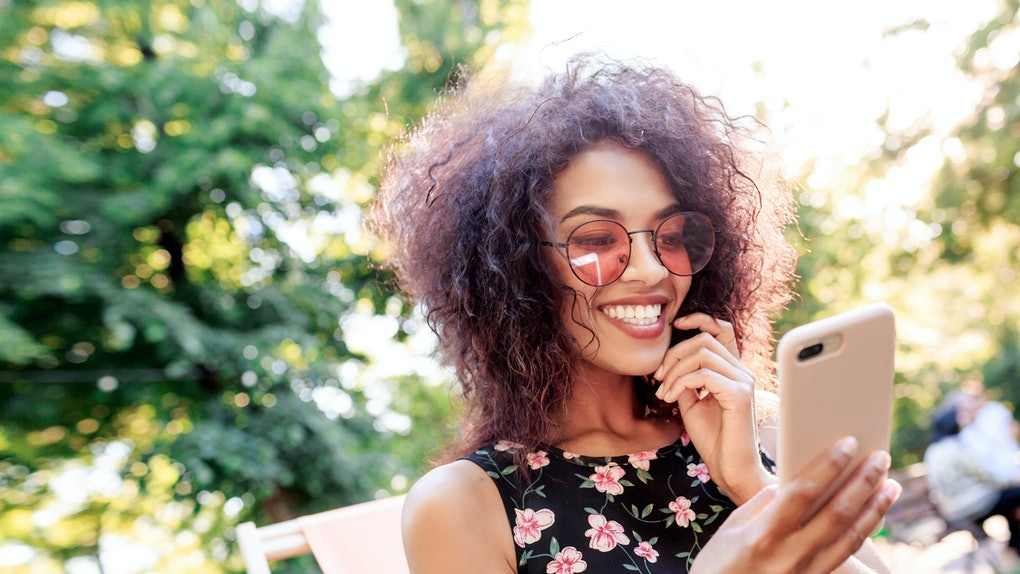 A happy woman with rose-colored sunglasses in her backyard looks at her phone.