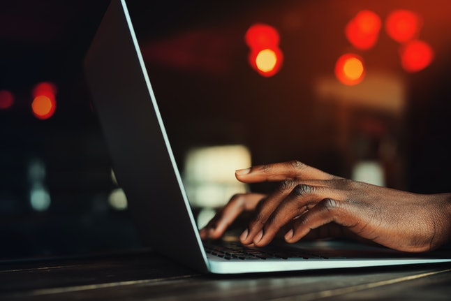 Black man's hands typing on laptop keyboard. Person working with laptop. Beautiful lights as backgro...