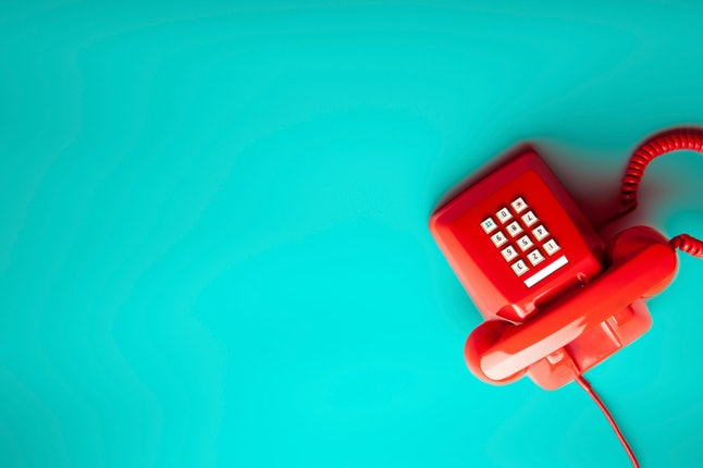 Top view of red telephone on green desk or background, waiting phone call, phone ringing, vintage, c...