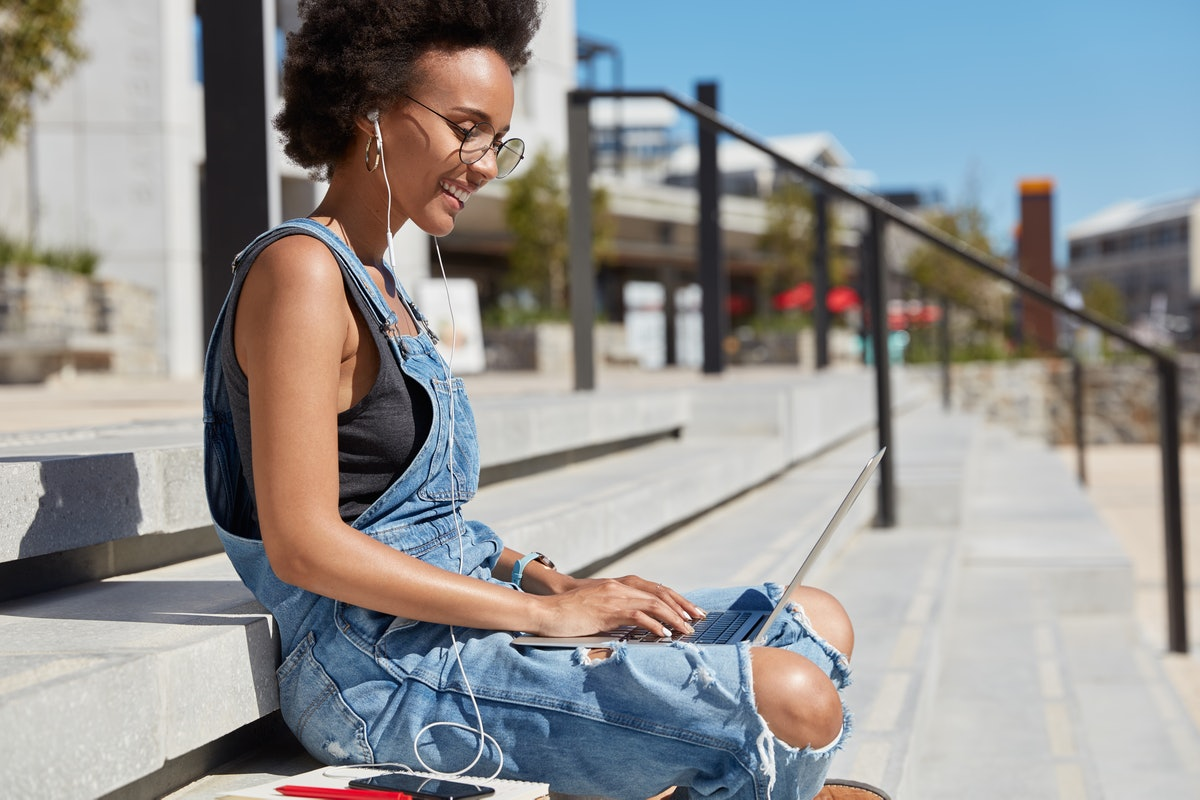 Sideways shot of black satisfied young woman checks email box on laptop computer, reads news, wears ragged denim dungarees, sits on steps against city background, relaxes outside in summer day