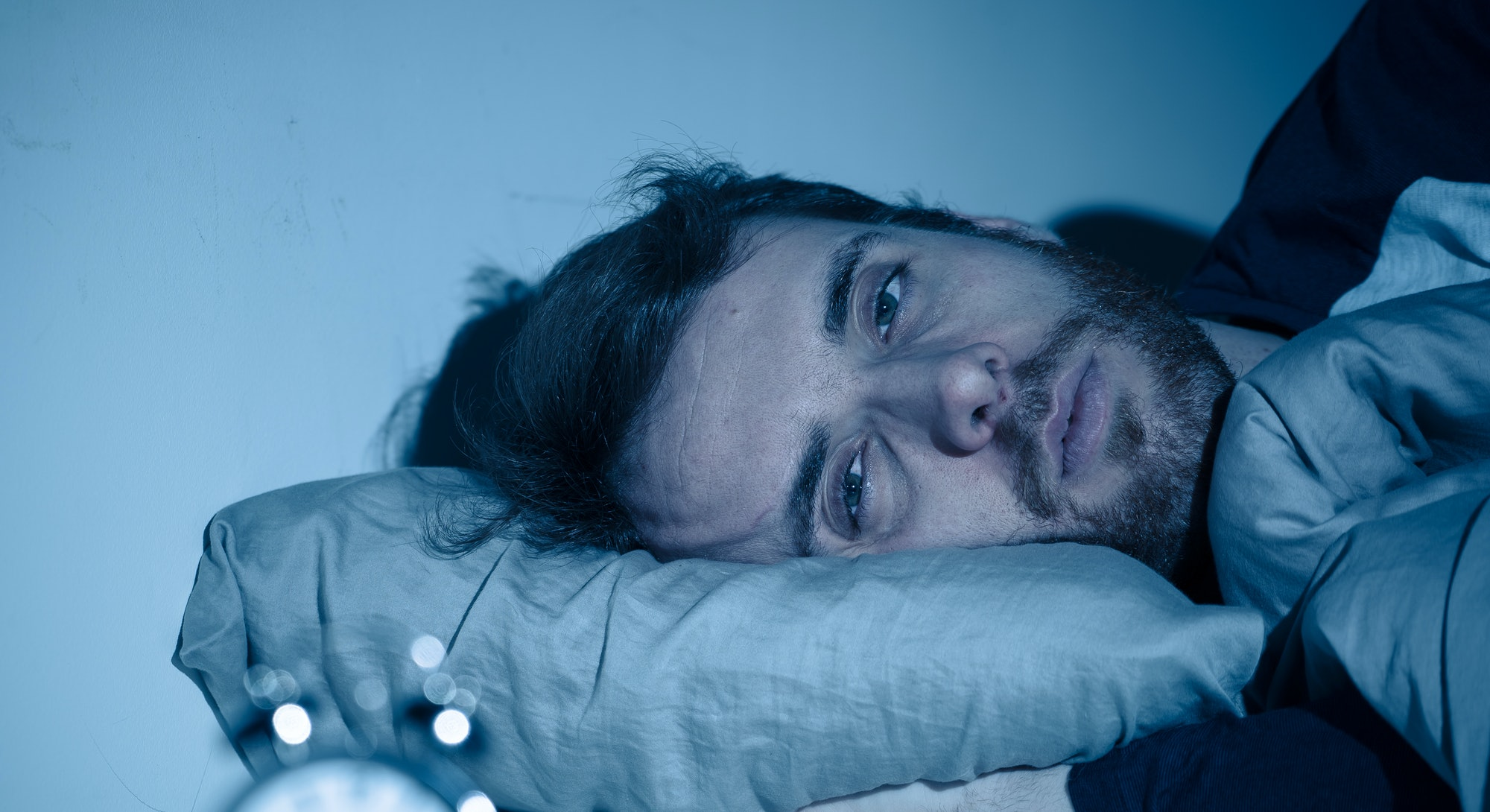 Sleepless and desperate young caucasian man awake at night not able to sleep, feeling frustrated and...