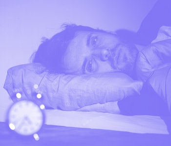 Sleepless and desperate young caucasian man awake at night not able to sleep, feeling frustrated and worried looking at clock suffering from insomnia in stress and sleeping disorder concept.