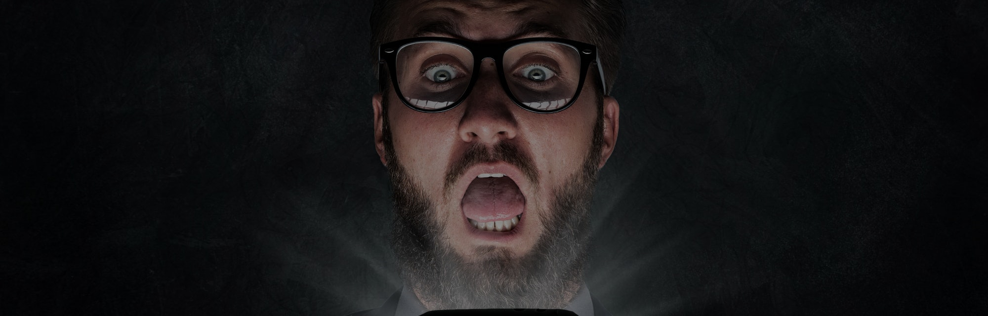 Nerd with glasses is shocked after reading a sms