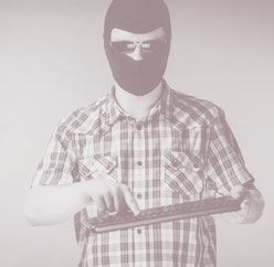 Crazy hacker man. Unrecognizable guy wearing black balaclava holding computer keyboard. Hate speech on the internet.