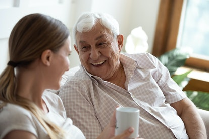 Head shot focus on happy old man talking with smiling grown up adult daughter, sitting together on sofa at home. Pleasant young woman communicating, having fun, laughing with retired 80s father.