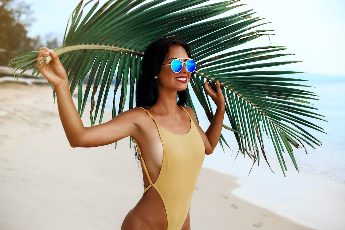 incredibly beautiful sexy girl models in a bikini on the sea shore of a tropical island with palm leaf, blonde brunette, bronze tan, travel summer vacation, fashion style