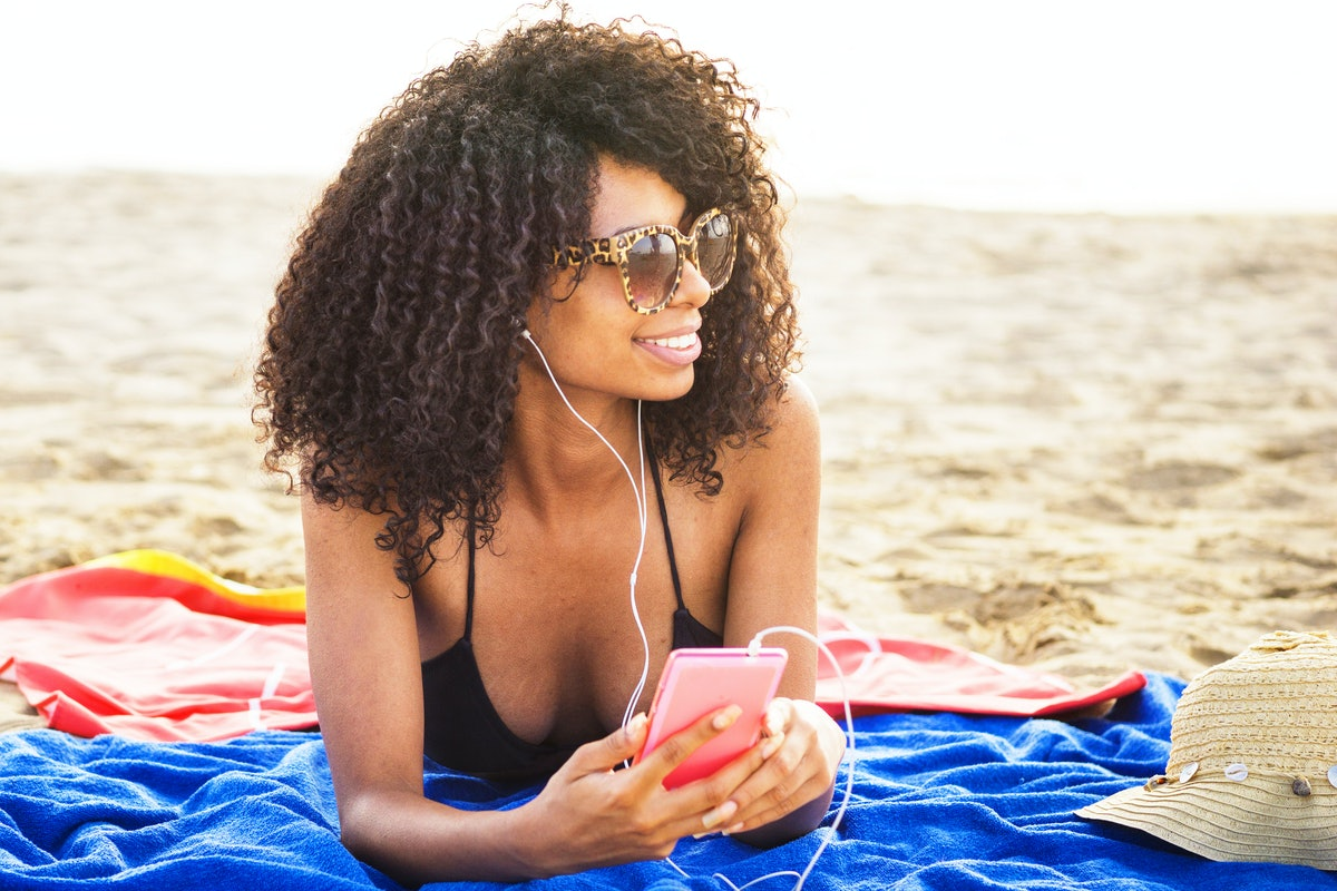 african origin girl relaxing on beach. afro hair woman wearing sunglasses lying on beach using phone listening to trendy  music with ear phones.