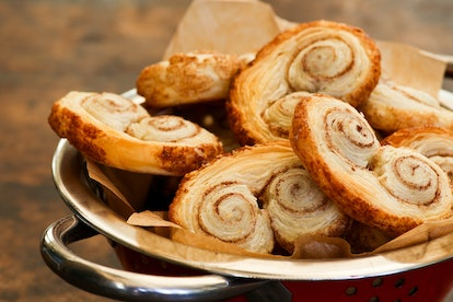 Homemade Gourmet danish puff pastries cinnamon puff pastry scrolls palmiers are also called palm leaf, butterfly shape, elephant ears, french hearts, shoe-soles in tin bowl with backing paper