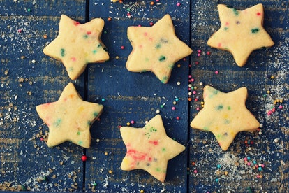 Overhead view of homemade Xmas star sugar cookies with colorful sprinkles on festive blue wooden background