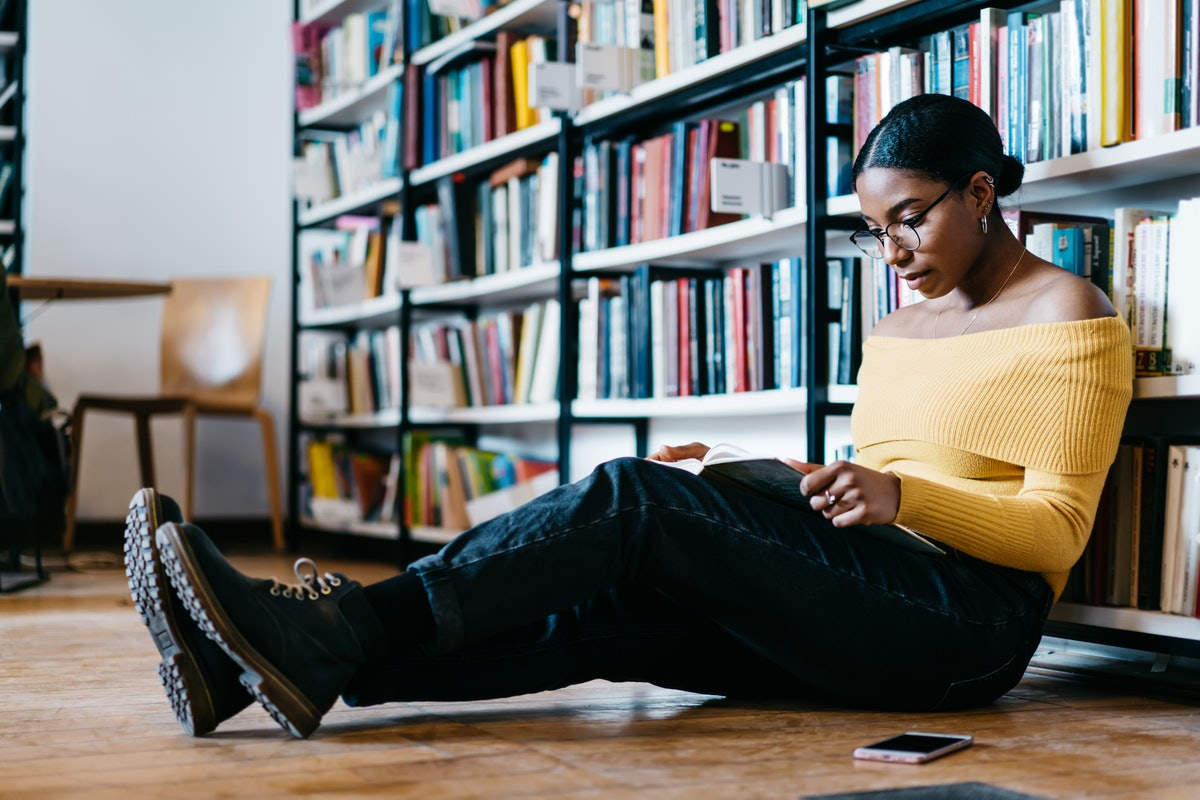 Pensive african american young woman in stylish eyeglasses for vision correction reading textbook sitting on floor near bookshelf.Concentrated dark sinned student spending leisure time in library