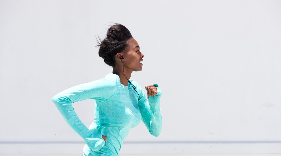 Side portrait of young black woman running outside with earphones