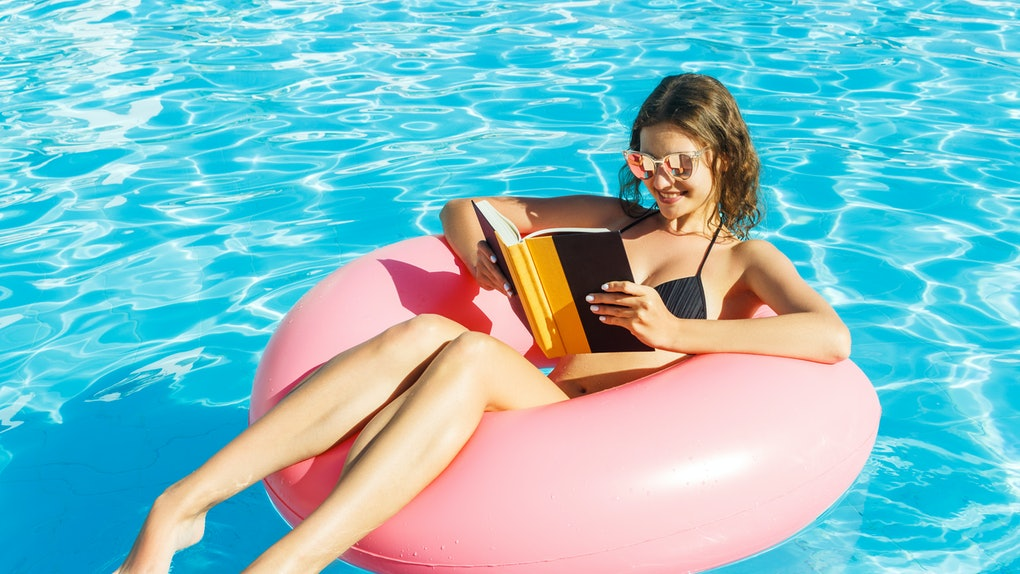 A happy girl in a bikini is floating in the pool on a pink tube with a book in her hand.