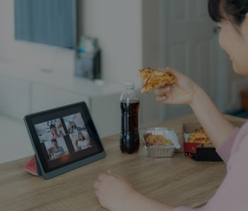 Asian woman virtual happy hour meeting party and eating food online together with her friend in video conference with digital tablet for a online meeting in video call for social distancing