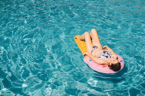 Woman lying on water matrass in the pool