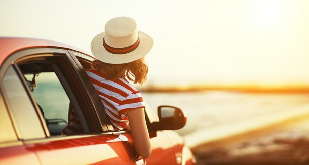 happy woman girl goes to summer travel trip in the  car