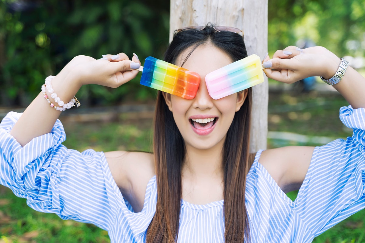 A woman smiles while holding up popsicles to her eyes in the summer.