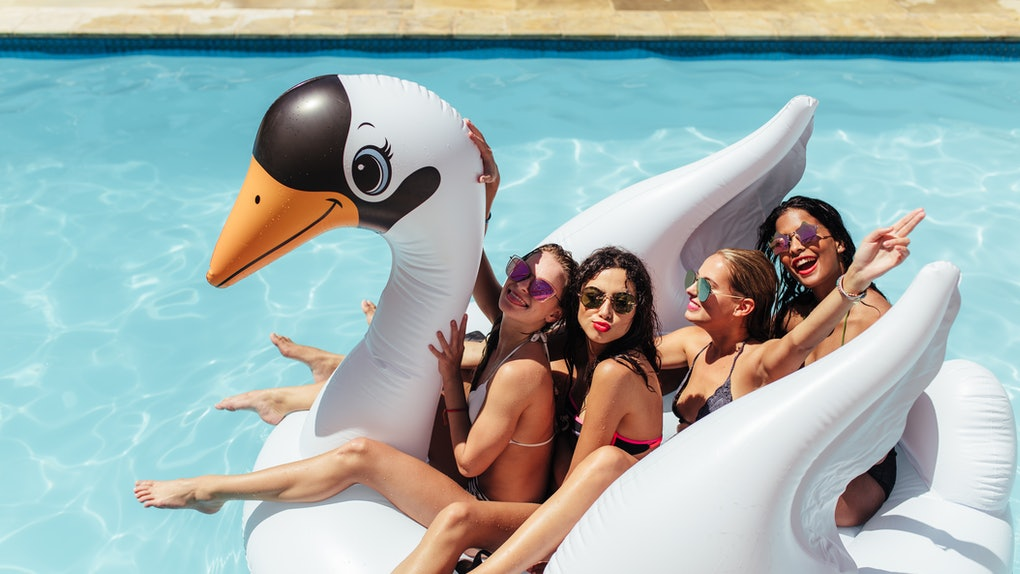 A group of friends sit on an inflatable swan pool float in the pool during the summer.