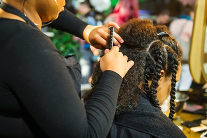 Close up african hairstylist braided hair of afro american female client in the barber salon. Black ...