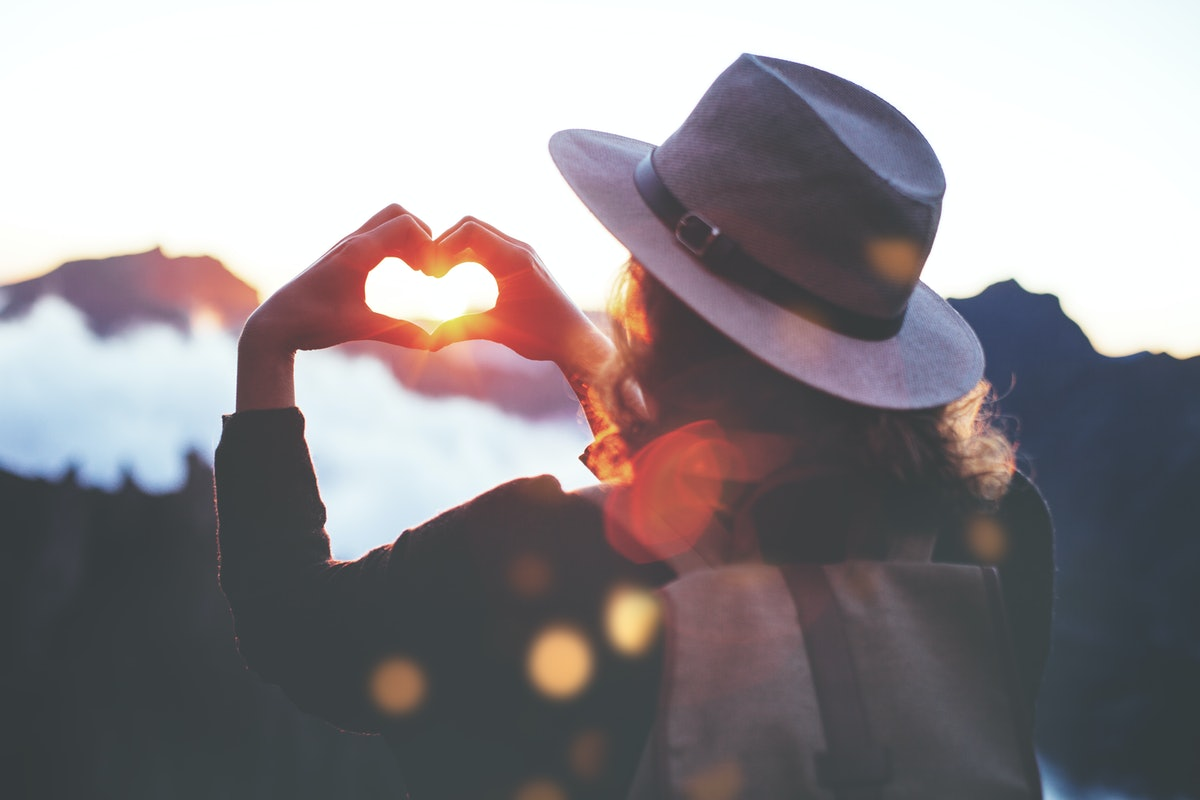 Young traveler woman with backpack and hat standing on edge of cliff at sunset and making by hands in shape of love heart.
