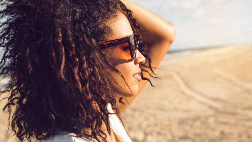 Side view portrait of a young afro american woman in sunglasses enjoying sun on a beach