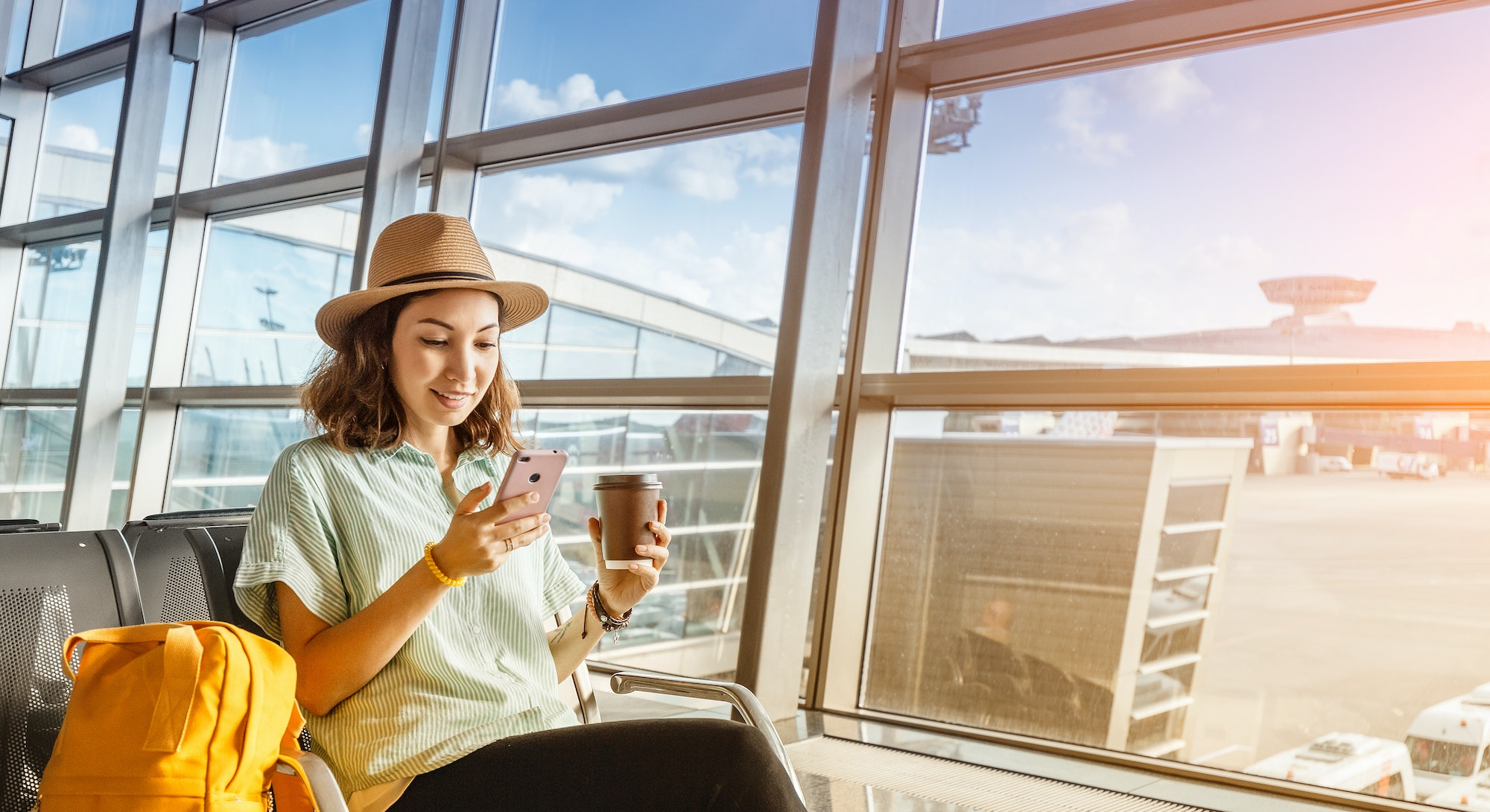 Asian girl waiting for departure at the airport on your vacation. Uses a smartphone and drinks coffee
