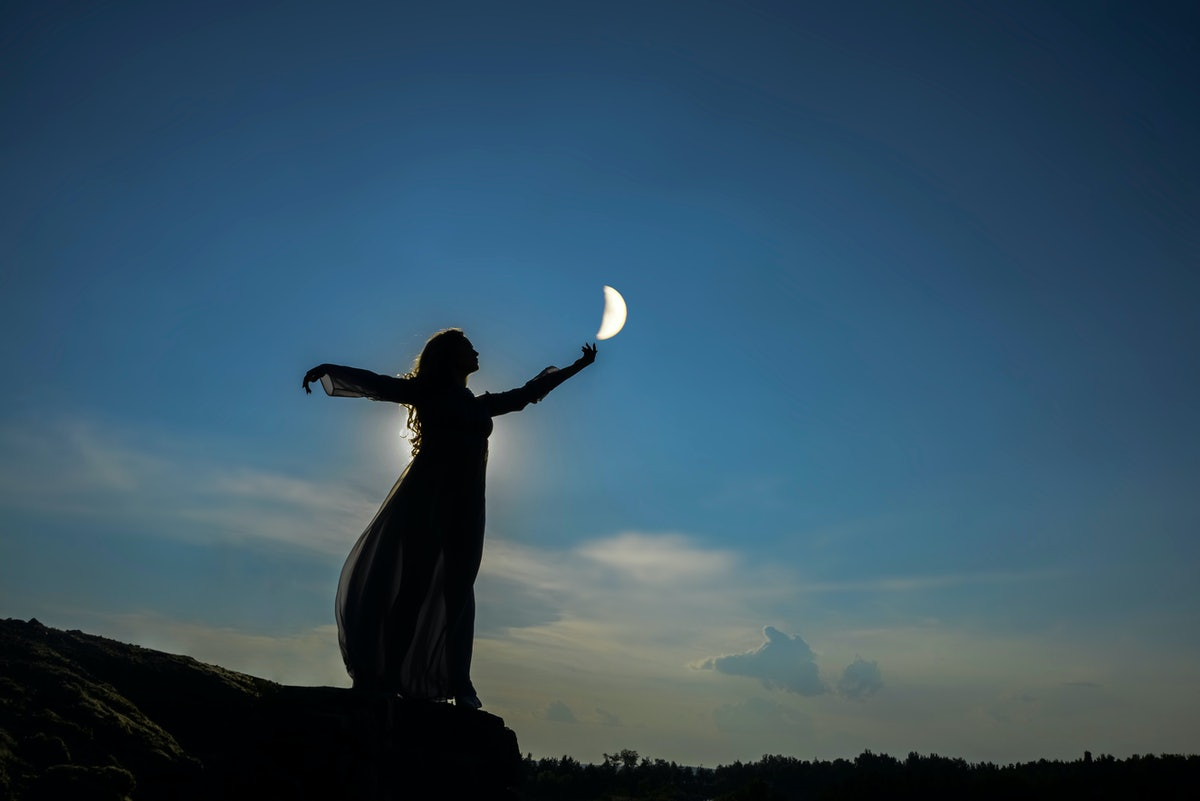 silhoutee of woman standing on top of mountain.  female hold in hand  growing moon above forest tree...