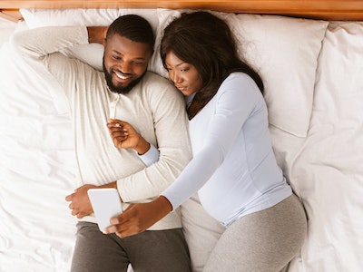 Married pregnant black couple taking selfie on smartphone while resting on bed at home, top view