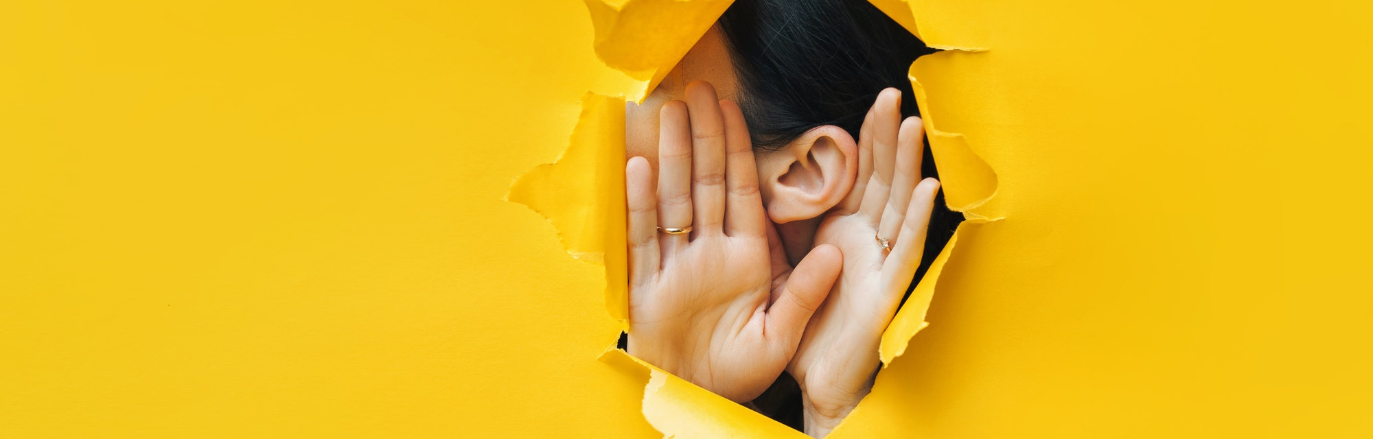 Female ear and hands close-up. Copy space. Torn paper, yellow background. The concept of eavesdropping, espionage, gossip and the yellow press.