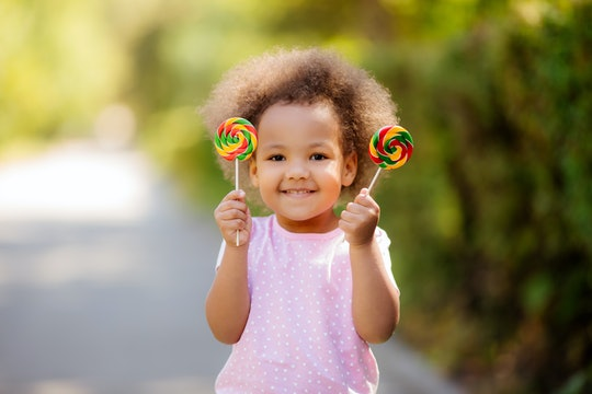 little African American girl in the summer on a walk smiling holding colorful candies