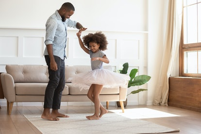 Loving black dad holding hand of child daughter dancing with his child princess wearing skirt, happy young african father and little cute daughter playing in living room enjoy time together at home