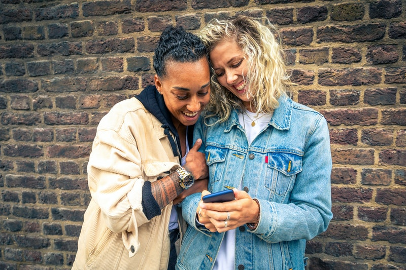 Happy girlfriends looking at a smartphone and having fun - Multiracial lesbian couple, millennials women, having fun together in London - LGBTQ concept with mixed race beautiful couple