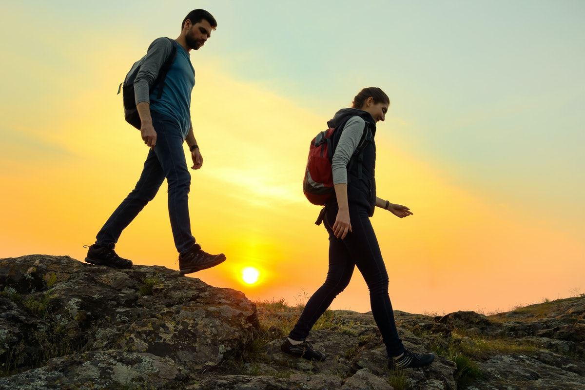 Couple of Young Happy Travelers Hiking with Backpacks on the Beautiful Rocky Trail at Warm Summer Su...