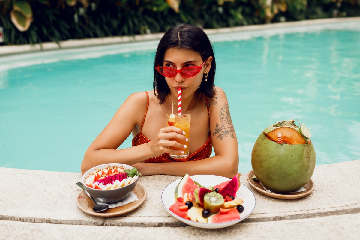 Confident  brunette tan woman in red cat eyes sunglasses   relaxing in   pool  with plate of exotic fruits  during tropical vacation.  Stylish tattoo.