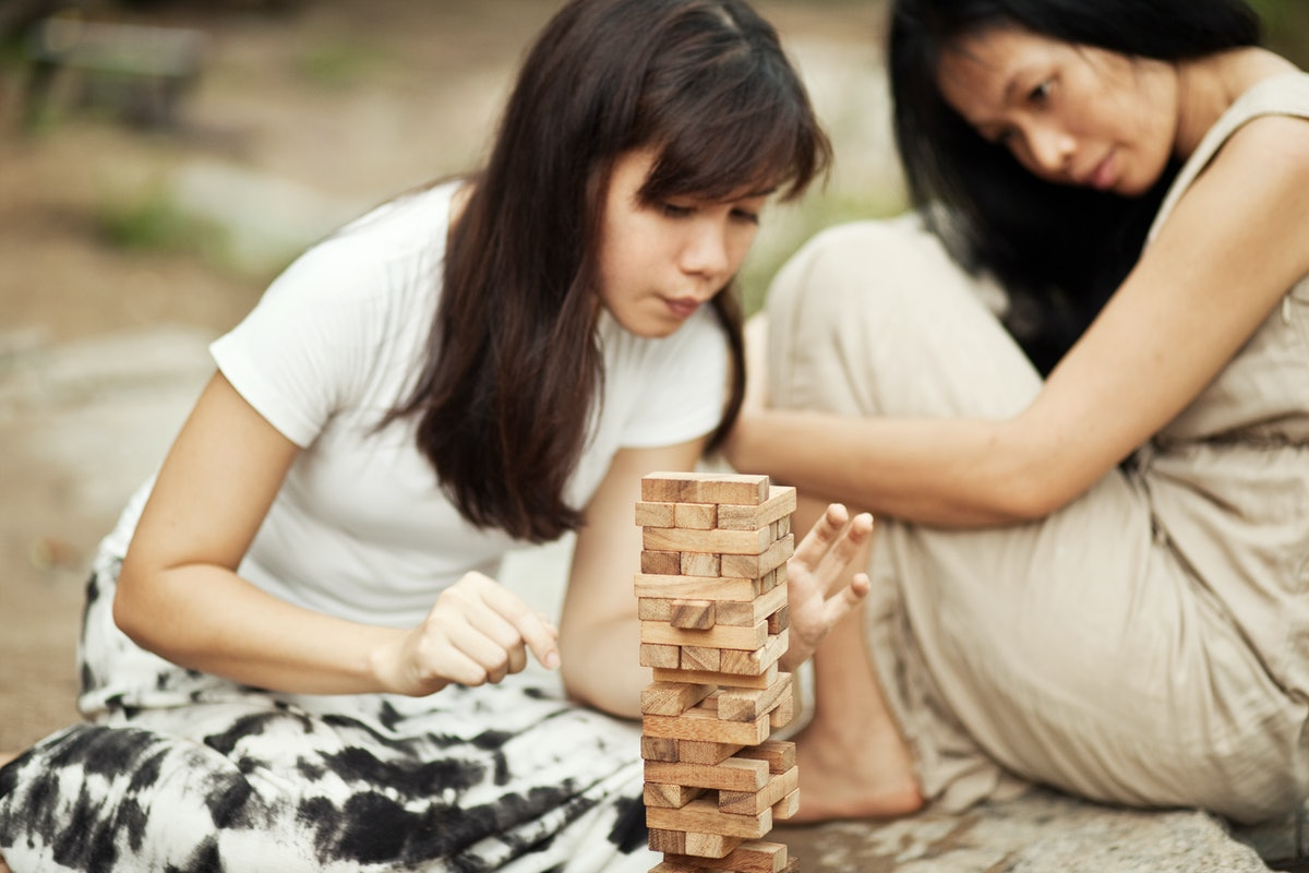 A woman pulls a block out of a Jenga tower outside.