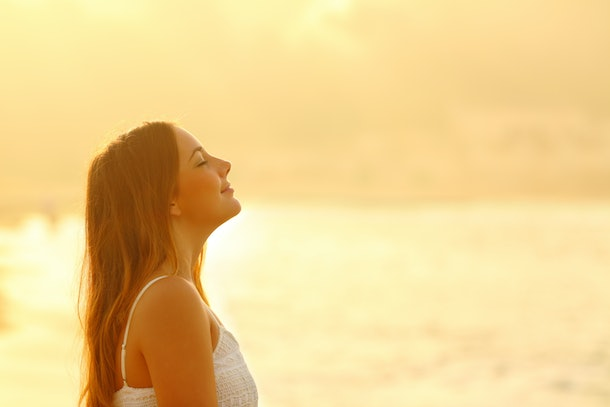 Side view portrait of woman at sunset relaxing breathing fresh air deeply on the beach