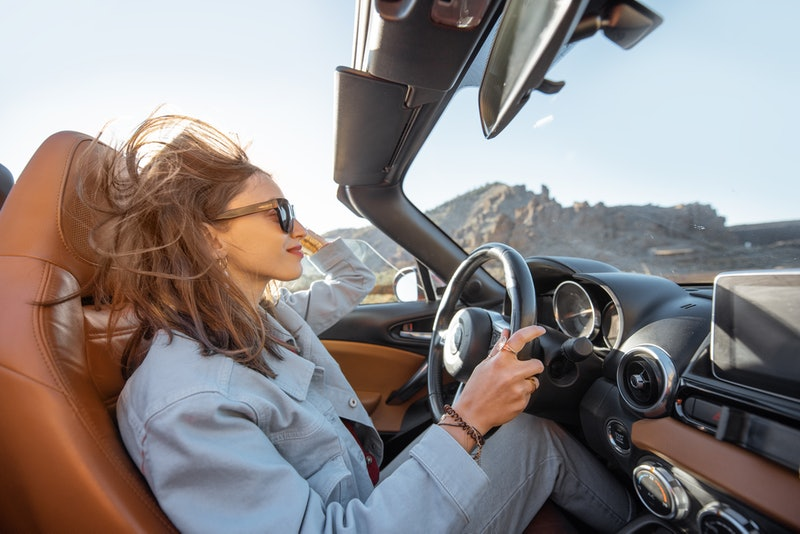 Happy woman driving convertible car while traveling on the desert road. Carefree lifestyle and travel concept