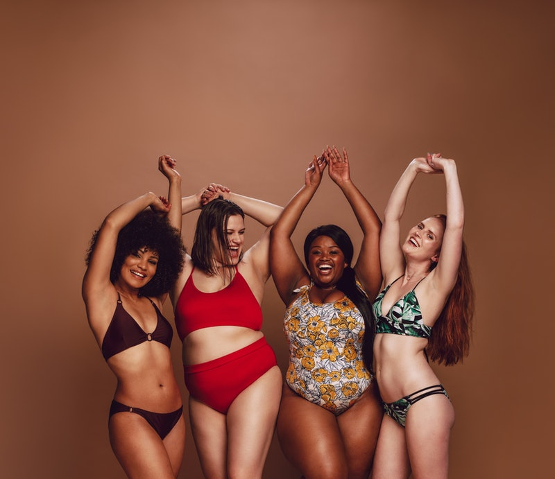 Group of different size women in bikinis dancing together. Multi-ethnic women in swimwear enjoying themselves in studio.