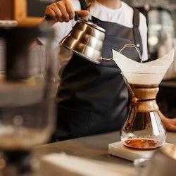 Professional barista preparing coffee using chemex pour over coffee maker and drip kettle. Alternati...