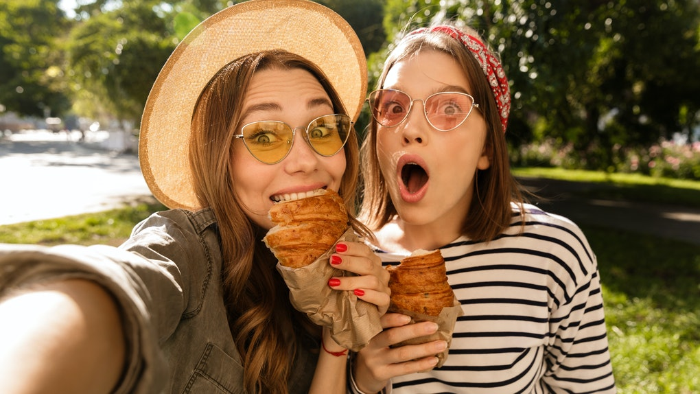 Two happy young girls friends having fun at the park, taking a selfie, holding croissants