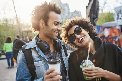 Couple strolling in park and drinking coffee while talking and enjoying spending time together