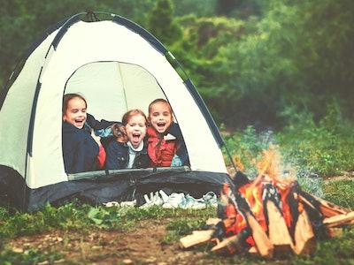 Children's tourism. Happy kids  girls in campaign in a tent near fire