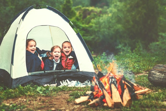 Children's tourism. Happy kids  girls in campaign in a tent near fire