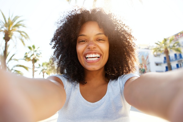 Selfie portrait of laughing black woman outside with curly hair