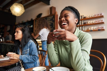 Young African American woman laughing while sitting in a cafe drinking coffee and hanging out with friends