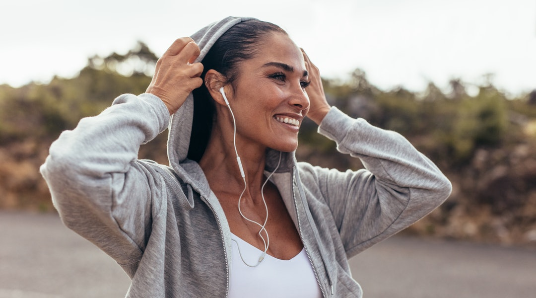 Fitness woman wearing a hooded shirt walking outdoors. Smiling female on early morning walk.