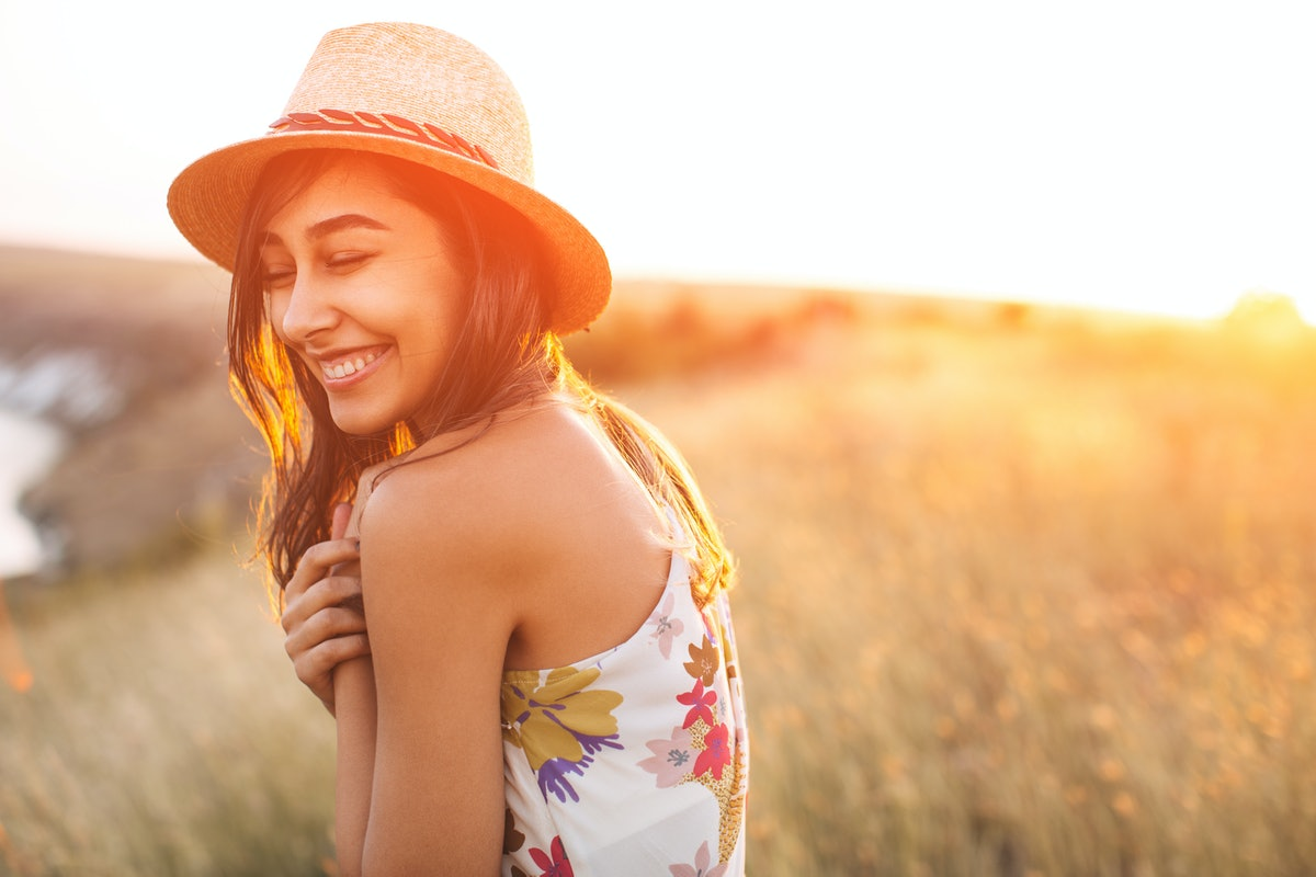 Lovely girl in stylish hat and summer dress smiling with closed eyes. Laughing young woman with sun ...