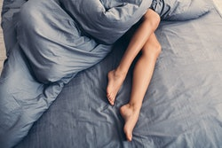 Perfect legs of sleeping woman in bed, top view, copy space