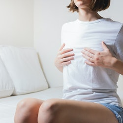 Woman sits on a bed and holds her breasts. Concept of breast pain, breast cancer awareness or menstrual pain